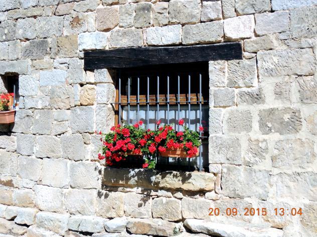 Una ventana con dintel de madera reja y flores - Dintel de madera ...